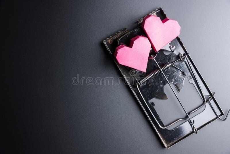 Forma rossa del cuore della scatola di uso della trappola per topi come esca sui wi neri del fondo fotografia stock libera da diritti