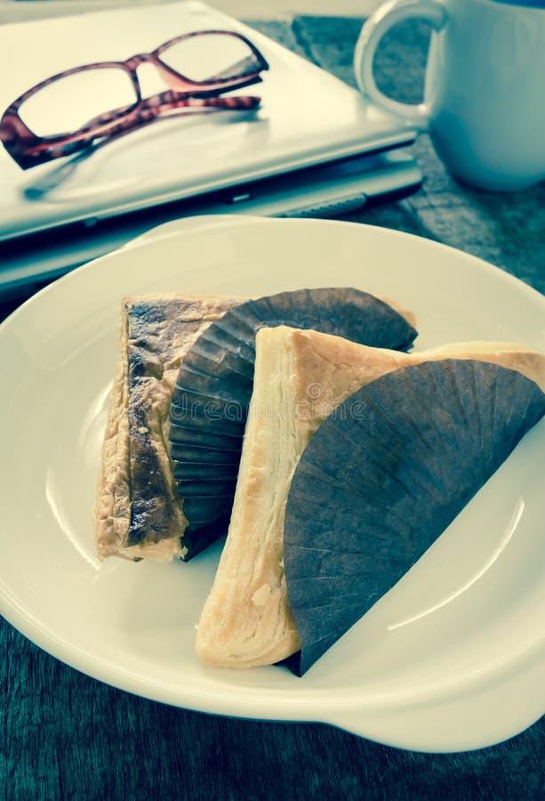 Forma triangular de la empanada en el plato blanco, filtro del efecto del vintage imagen de archivo