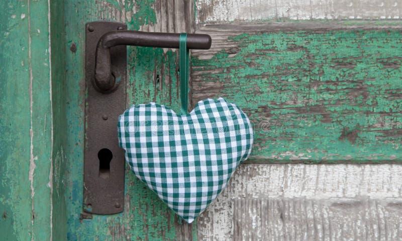 Forma verde a quadretti del cuore che appende sulla maniglia di porta per nozze, fotografia stock