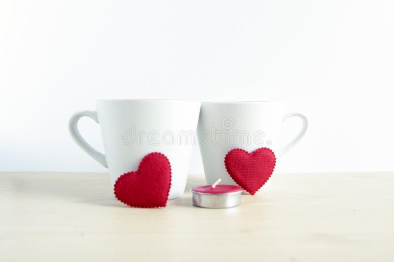 Forma vermelha do coração com as duas canecas brancas na tabela de madeira conceito para v imagens de stock royalty free