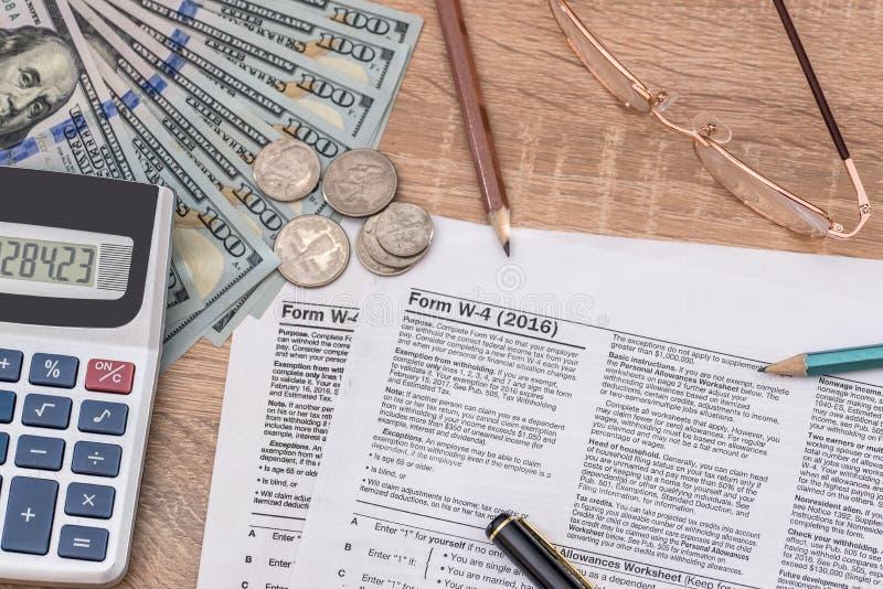 Forma w4 di imposta con la penna ed il dollaro americano, calcolatore fotografia stock