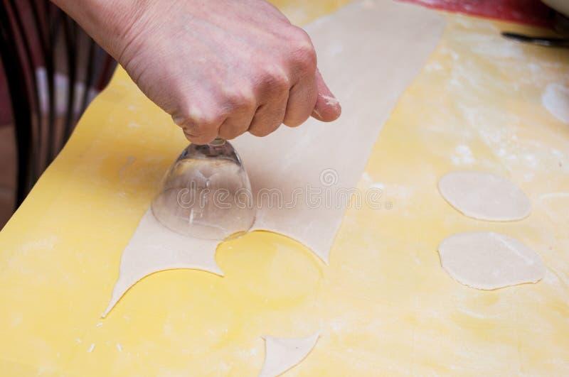 Formación de espacios en blanco de una pasta para el pelmeni hecho en casa por las manos foto de archivo libre de regalías
