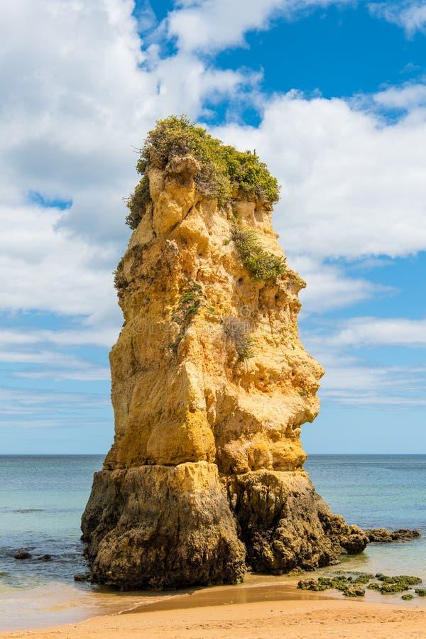 Formación de roca alta en una playa arenosa en un mar azul de la aguamarina tranquila fotografía de archivo libre de regalías