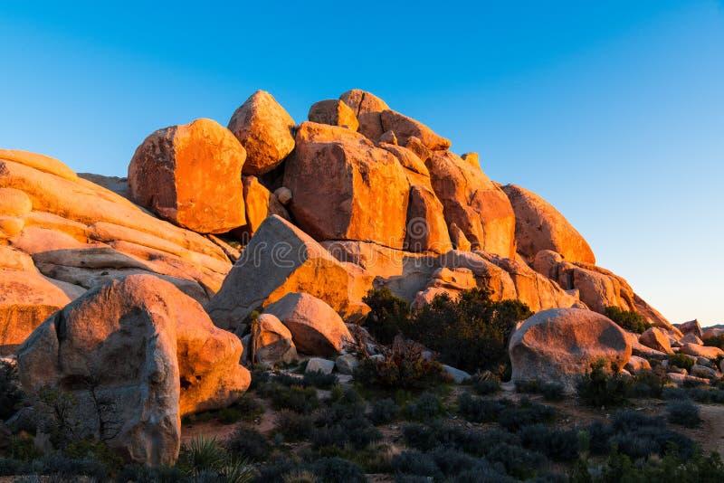 Formación de roca de cantos rodados enormes de la piedra arenisca que brillan intensamente en la luz de oro de la puesta del sol foto de archivo libre de regalías
