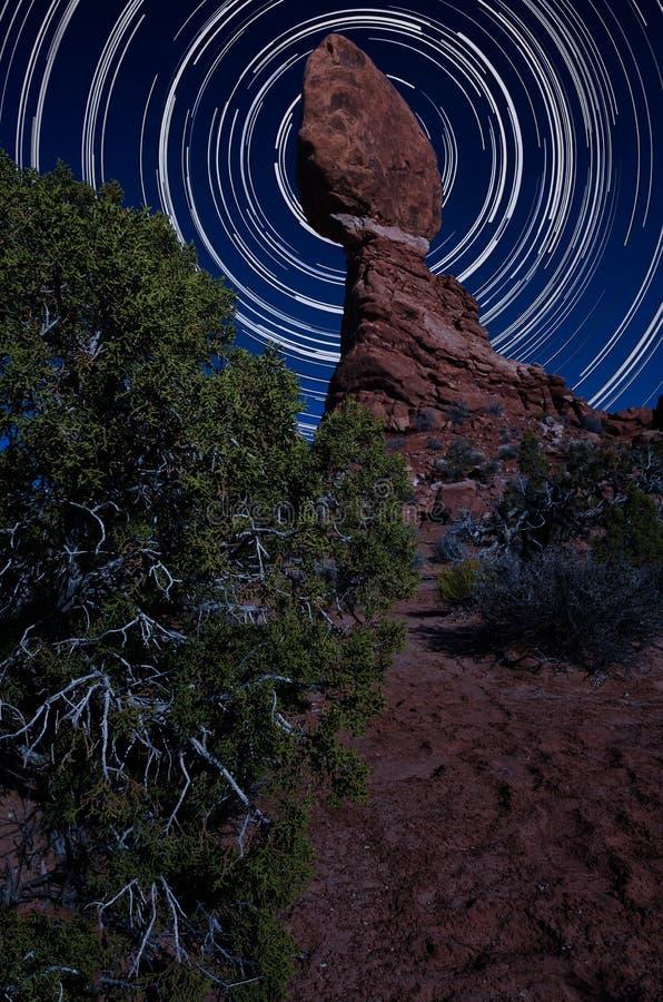 Roca equilibrada en la noche con los rastros de la estrella imagen de archivo libre de regalías