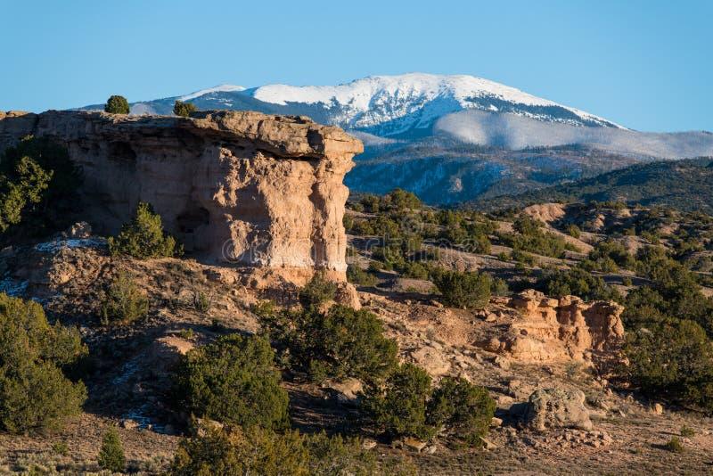 Formación de roca roja con un pico de montaña coronado de nieve cerca de Santa Fe, New México fotos de archivo libres de regalías