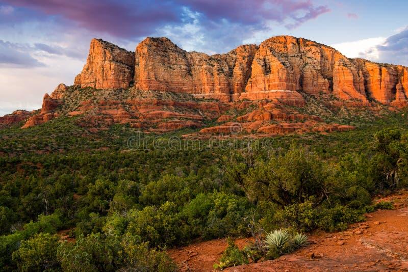 Formación de roca roja hermosa iluminada por puesta del sol sobre un paisaje que pone en contraste del enebro y de arbustos verde foto de archivo