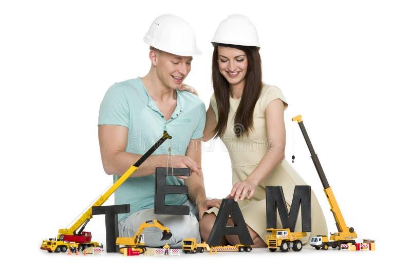 Formación de un equipo: Equipo-palabra alegre del edificio del hombre y de la mujer. imagen de archivo libre de regalías