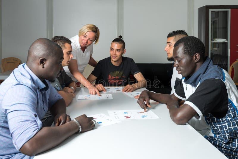 Formación lingüística para los refugiados en un campo alemán imagen de archivo