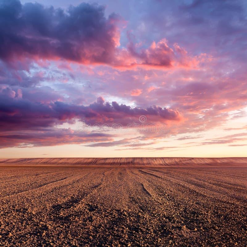 Formaciones cultivadas de la tierra y de la nube en la puesta del sol foto de archivo