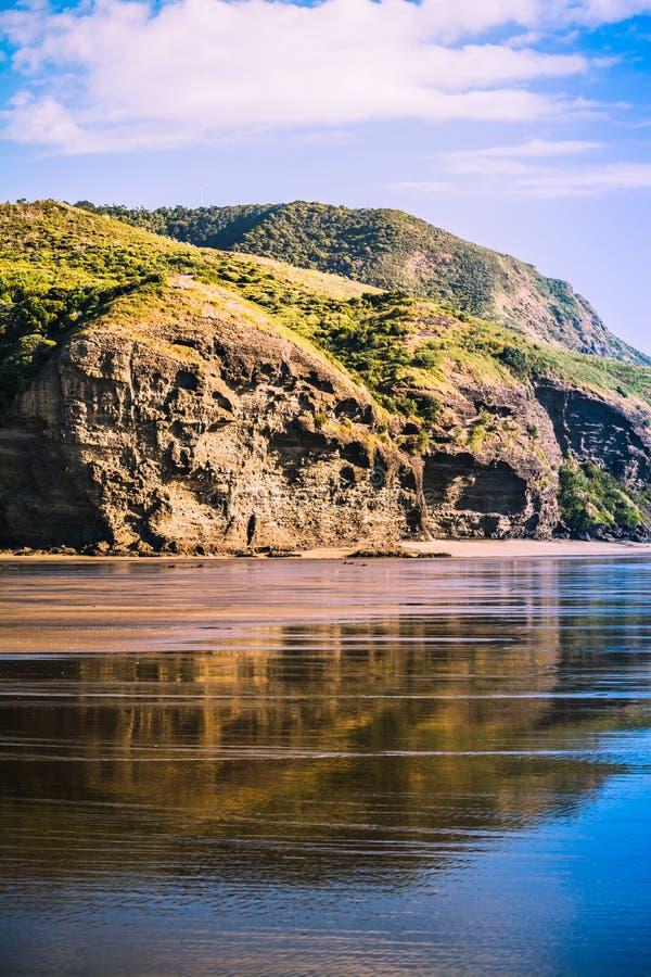 Formaciones de roca magníficas reflejadas en las ondas de marea apacibles que corren sobre la orilla fotos de archivo