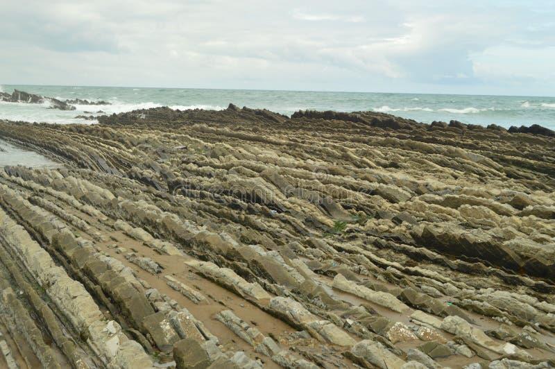 Formaciones geológicas en la playa con final en el mar del tipo la UNESCO vasca del flysch de la ruta de Geopark Juego filmado de fotos de archivo libres de regalías