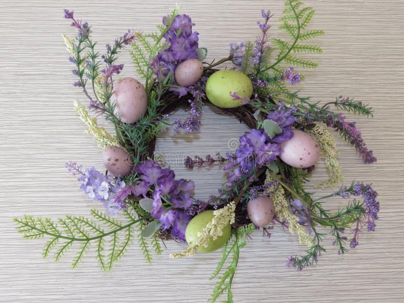 Formad korg för påsk rede av gröna blåa purpurfärgade blommor och färgrika ägg på grå bakgrund som bakgrundsägg många quail arkivfoton