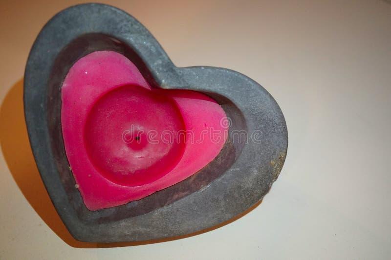 formad stearinljushj?rtared Röd stearinljus för hjärtaform som omges med den svarta stenen royaltyfria bilder