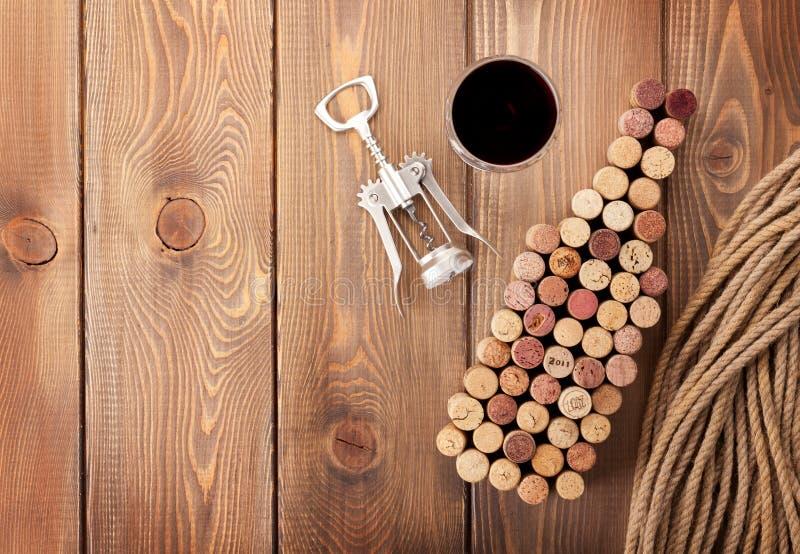 Formade korkar för vinflaska, exponeringsglas av rött vin och korkskruv fotografering för bildbyråer