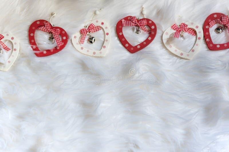 Formade trähjärta fem xmas-prydnader på vitt mjukt tyg med band royaltyfri foto