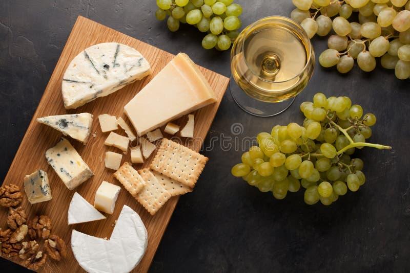 Formaggi assortiti con l'uva bianca, le noci, i cracker ed il vino bianco su un bordo di legno Alimento per una data romantica su fotografie stock