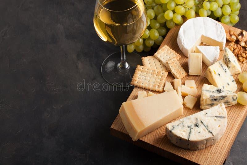Formaggi assortiti con l'uva bianca, le noci, i cracker ed il vino bianco su un bordo di legno Alimento per una data romantica su immagine stock