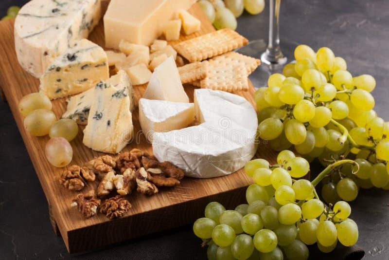 Formaggi assortiti con l'uva bianca, le noci, i cracker ed il vino bianco su un bordo di legno Alimento per una data romantica su immagini stock libere da diritti