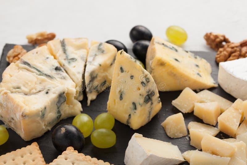 Formaggi assortiti con l'uva bianca, noci, cracker e su un bordo di pietra Alimento per una data romantica su un fondo leggero immagini stock