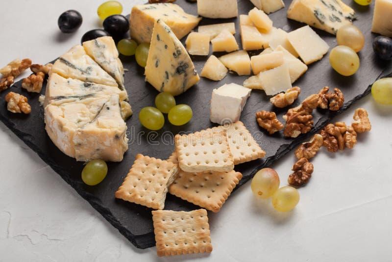 Formaggi assortiti con l'uva bianca, noci, cracker e su un bordo di pietra Alimento per una data romantica su un fondo leggero fotografia stock libera da diritti
