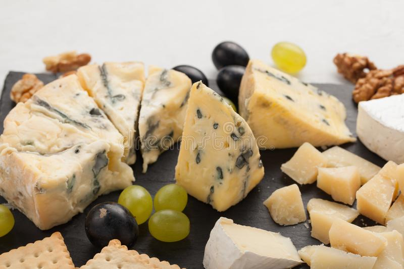 Formaggi assortiti con l'uva bianca, noci, cracker e su un bordo di pietra Alimento per una data romantica su un fondo leggero fotografia stock