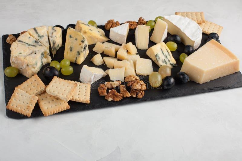 Formaggi assortiti con l'uva bianca, noci, cracker e su un bordo di pietra Alimento per una data romantica su un fondo leggero fotografie stock