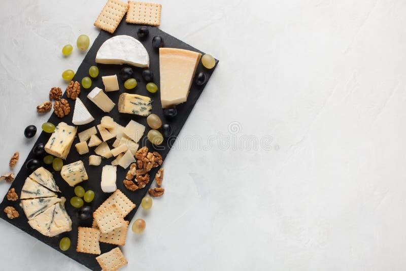 Formaggi assortiti con l'uva bianca, noci, cracker e su un bordo di pietra Alimento per una data romantica su un fondo leggero pr immagini stock libere da diritti
