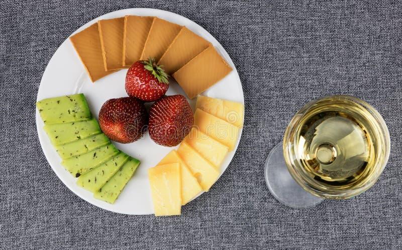 Formaggio affettato su un piatto con un bicchiere di vino fotografia stock libera da diritti