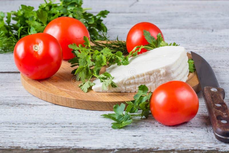Formaggio bianco, coltello, prezzemolo, pomodori su un fondo dei bordi di legno fotografie stock libere da diritti