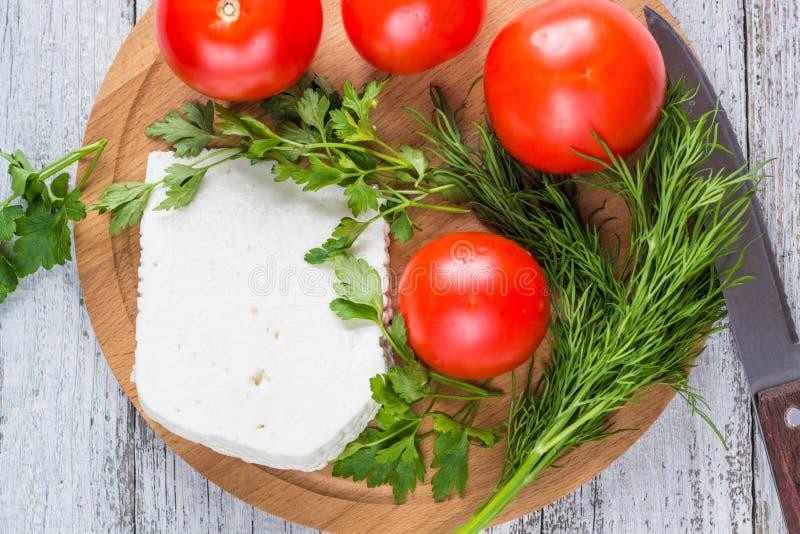 Formaggio bianco, coltello, prezzemolo, pomodori su un fondo dei bordi di legno immagine stock