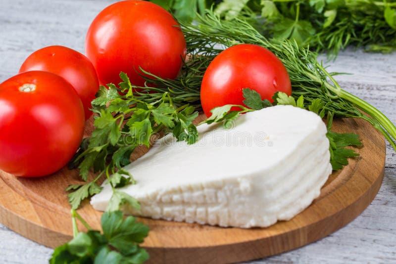 Formaggio bianco, coltello, prezzemolo, pomodori su un fondo dei bordi di legno fotografie stock