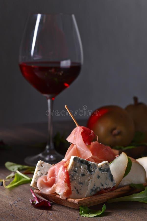Formaggio blu con il prosciutto di Parma, la pera ed il vino rosso fotografie stock