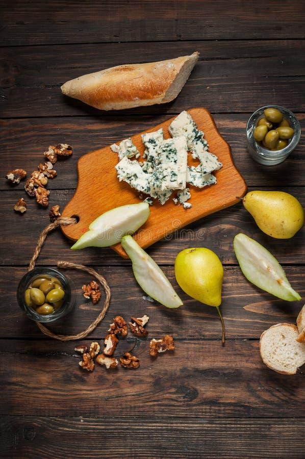 Formaggio blu con le noci, l'oliva e le pere sulla tavola rustica fotografia stock libera da diritti