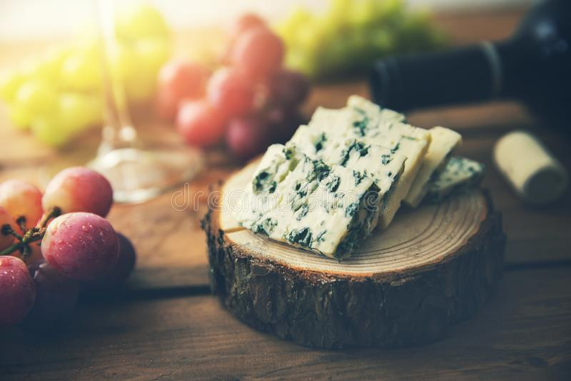 Formaggio blu di Dor sulla fetta di legno del ceppo con l'uva e la bottiglia di vino fotografie stock libere da diritti