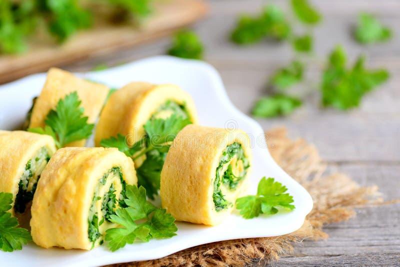 Formaggio casalingo e rotoli dell'omelette farciti prezzemolo Tagli l'omelette fritta con formaggio grattugiato e le erbe finemen immagine stock