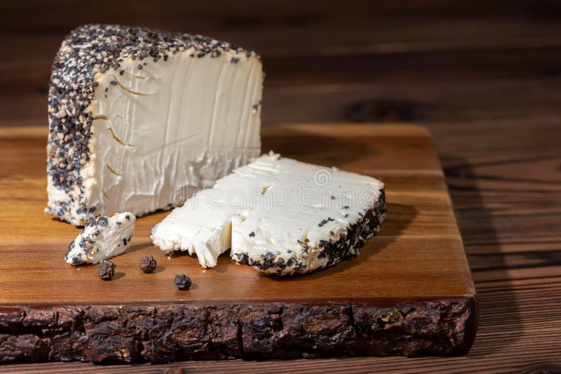 formaggio con pepe nero grattato su struttura di legno immagini stock libere da diritti