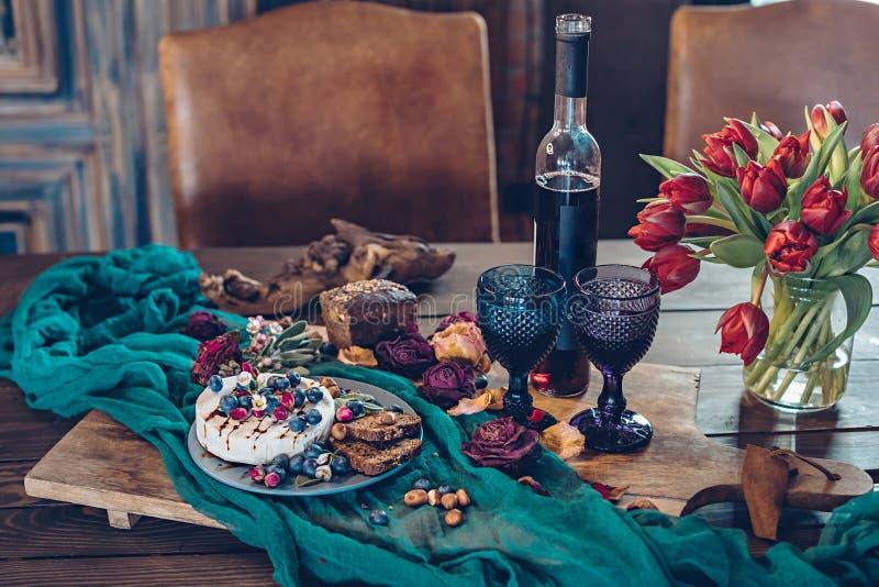 Formaggio del camembert con i mirtilli, il pane, i dadi ed il vino rosso decorati con i fiori immagini stock libere da diritti