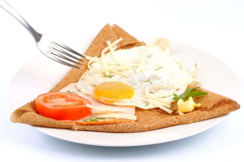 Formaggio del prosciutto dell'uovo di Galette in un piatto su fondo bianco immagini stock