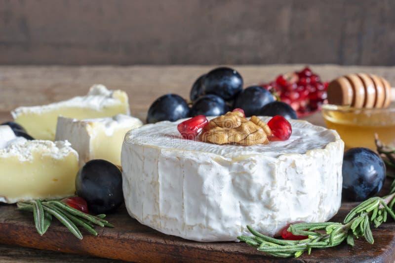 Formaggio delizioso del camembert con l'uva, i semi del melograno, le noci del miele ed i rosmarini sul tagliere di legno fotografia stock