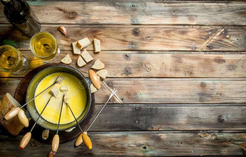 Formaggio delizioso della fonduta con le fette del pane ed il vino bianco immagine stock