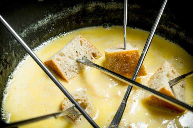 Formaggio delizioso della fonduta con le fette di pane fotografie stock