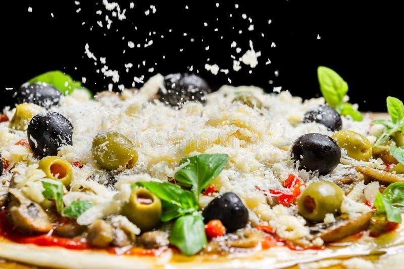 Formaggio di caduta su una pizza appena preparato immagine stock libera da diritti