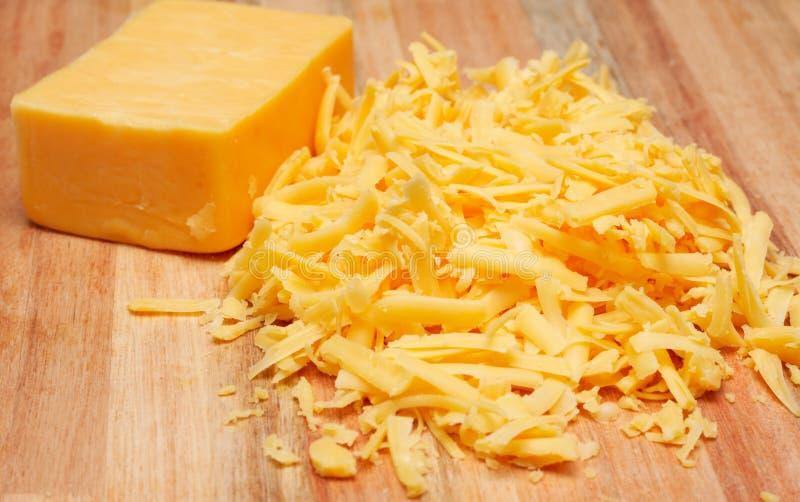 Formaggio di formaggio cheddar grattato sulla scheda di legno fotografia stock