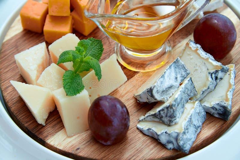 Download Formaggio E Frutti Sul Piatto Di Legno Fotografia Stock - Immagine di olio, prugne: 55357642