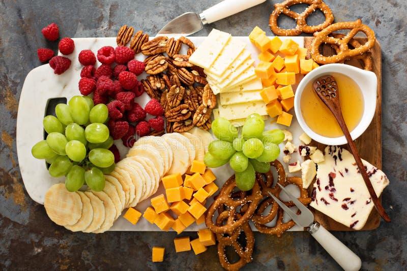 Formaggio e vassoio degli spuntini con miele e frutta fresca fotografia stock
