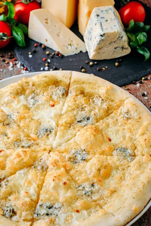 Formaggio ed ingredienti della pizza quattro su una fine di legno della tavola su immagine stock libera da diritti
