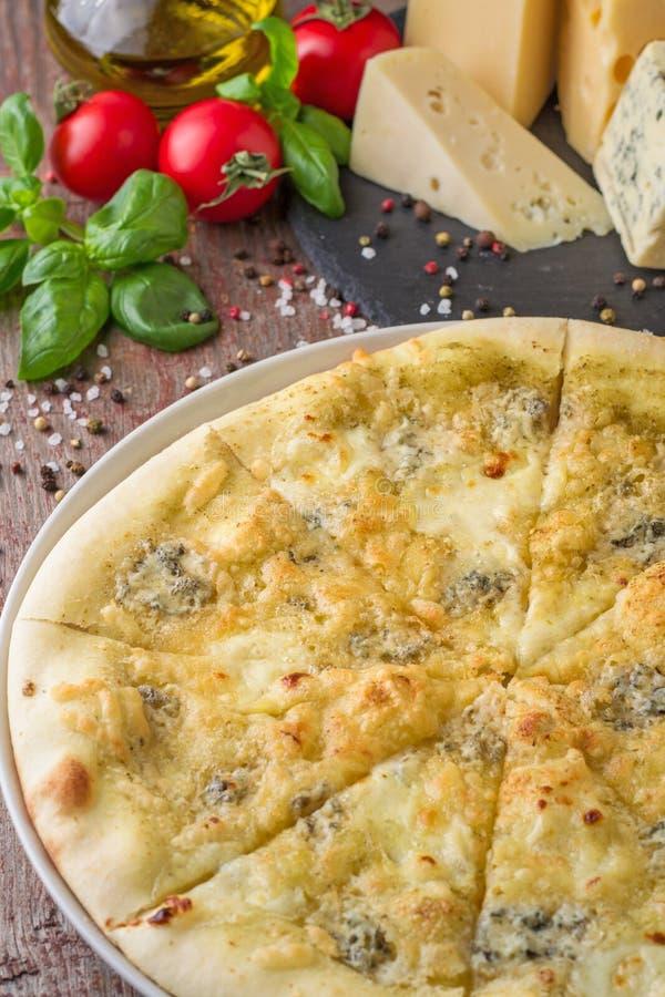 Formaggio ed ingredienti della pizza quattro sulla tavola di legno immagini stock libere da diritti