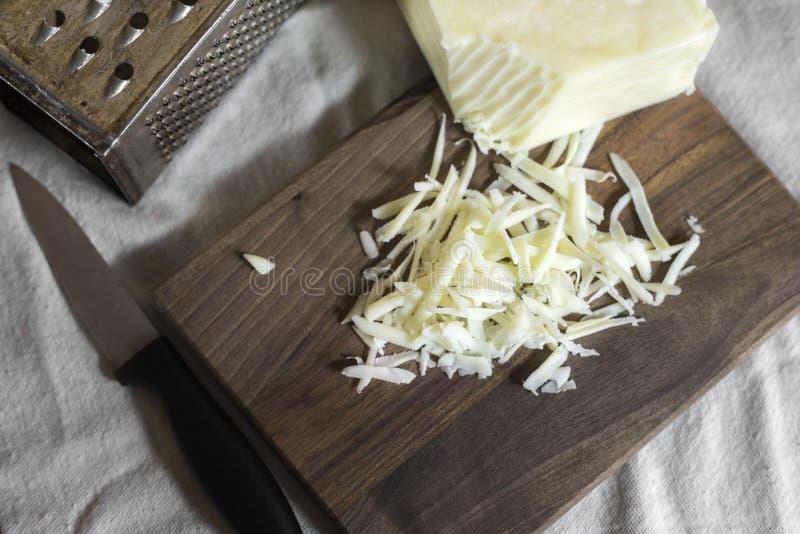 Formaggio grattugiato con la grattugia ed il coltello fotografia stock libera da diritti