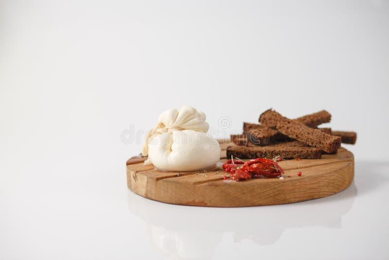 Formaggio italiano tradizionale Burrata su un bordo di legno con le spezie ed i pomodori seccati al sole fotografia stock libera da diritti
